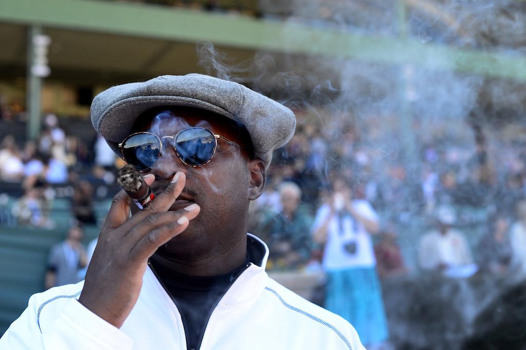 Description of . Eric Williams, of Chicago, enjoys a cigar during the Breeders' Cup at Santa Anita Park in Arcadia Friday, November 1, 2013. (Photo by Sarah Reingewirtz/Pasadena Star-News)