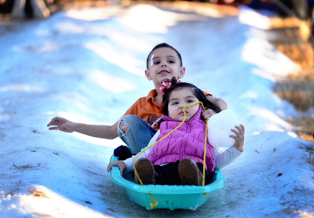 Description of . Max Cuevas, 6, of Los Angeles, and his cousin Jaileen Avalos, 1, go sledding during Montebello's annual Winter Wonderland at Montebello City Park Saturday, December 14, 2013. (Photo by Sarah Reingewirtz/Pasadena Star-News)