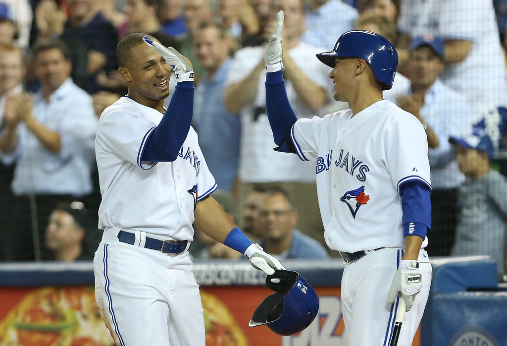 Description of . TORONTO, CANADA - SEPTEMBER 11: Moises Sierra #14 of the Toronto Blue Jays is congratulated by Ryan Goins #17 after scoring a run in the fourth inning after hitting a triple during MLB game action against the Los Angeles Angels of Anaheim on September 11, 2013 at Rogers Centre in Toronto, Ontario, Canada. (Photo by Tom Szczerbowski/Getty Images)