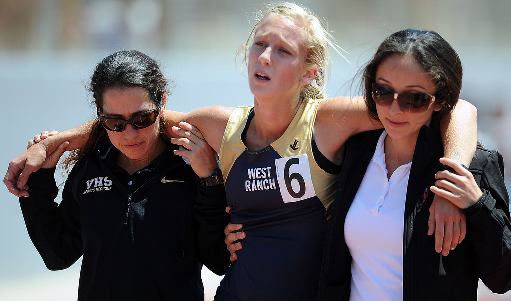 Description of . West Ranch's Taylor Welker is helped off the track after collapsing after the 1600 meters race during the CIF-SS track & Field championship finals in Hilmer Stadium on the campus of Mt. San Antonio College on Saturday, May 18, 2013 in Walnut, Calif.  (Keith Birmingham Pasadena Star-News)