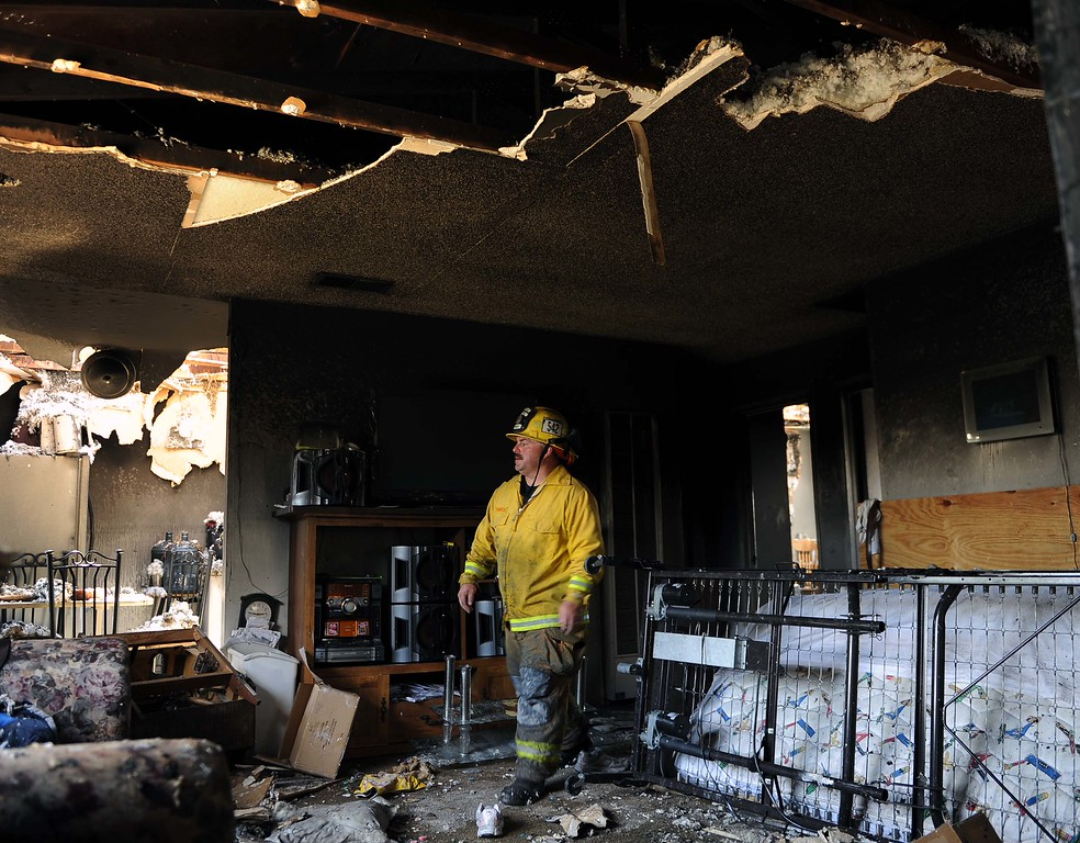 Description of . Cal Fire firefighter Lee Fonseca searches through a burned-out apartment after a fire at the complex Sunday morning displaced 72 residents in Highland on Sunday. (LaFonzo Carter/Staff Photographer)