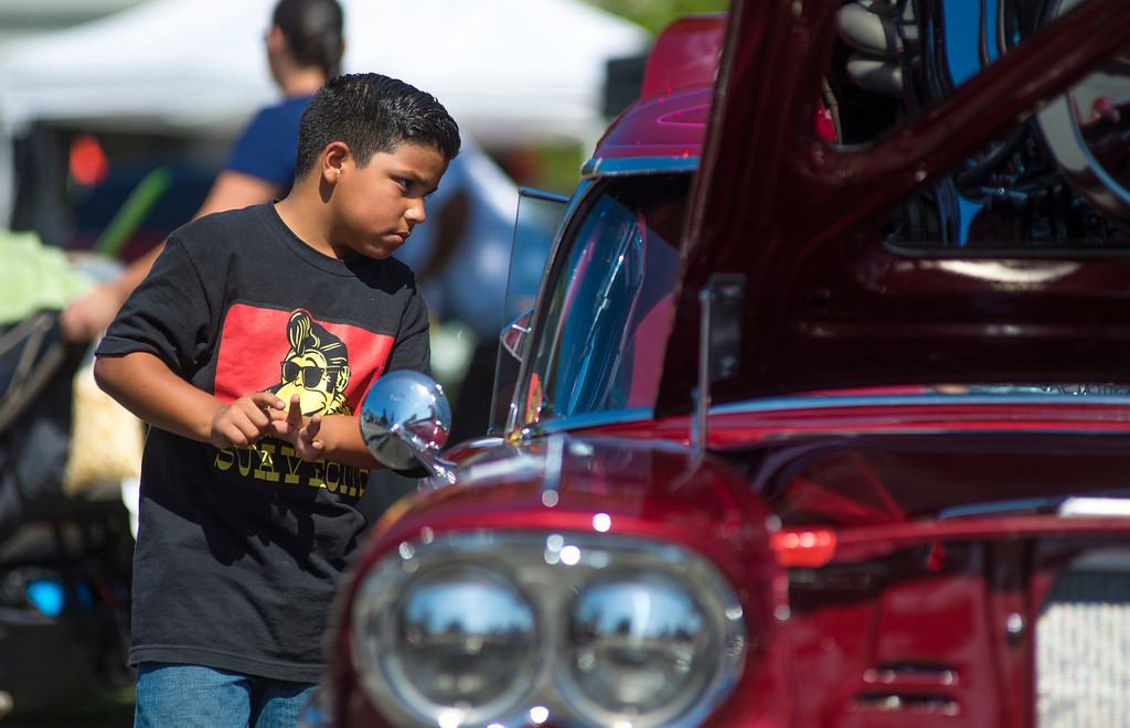 Description of . IDB-L-DBROUTE66-SAT-02 Gilbert Munoz, 6, of Ontario Checks out a customized 1958 Chevy Impala  . Classic cars line Euclid Ave in Ontario, for the