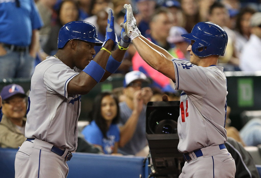 Description of . Mark Ellis #14 of the Los Angeles Dodgers is congratulated by Yasiel Puig #66 after hitting a 2-run home run in the tenth inning during MLB game action against the Toronto Blue Jays on July 24, 2013 at Rogers Centre in Toronto, Ontario, Canada. Dodgers won 8-3.   (Photo by Tom Szczerbowski/Getty Images)