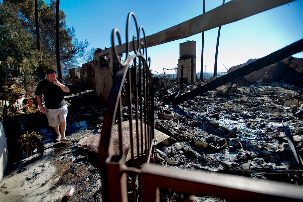 Description of . Greg Peterson walks through the remains of his home after it was destroyed by the Colby Fire in Glendora on Friday morning, Jan. 17, 2014. Glendora residents return to their homes this morning after the mandatory evacuations were lifted. (Photo by Watchara Phomicinda/ San Gabriel Valley Tribune)