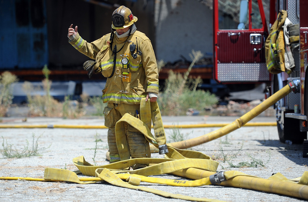Description of . Los Angeles County firefighters looks over water hoses during a 3-alarm fire at an abandoned warehouse near 9th Avenue and Clark Avenue on Tuesday, July 9, 2013 in City of Industry, Calif.  (Keith Birmingham/Pasadena Star-News)
