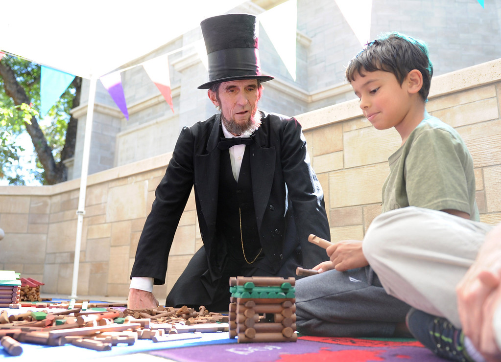 Description of . (John Valenzuela/Staff Photographer) Abraham Lincoln impersonator Robert Broski watches Aidan Barajas 7, of Redlands, as he uses Lincon Logs to builds a cabin during the 10th Annual Family Day at the A.K. Smiley Library in Redlands, Saturday Oct. 5, 2013.