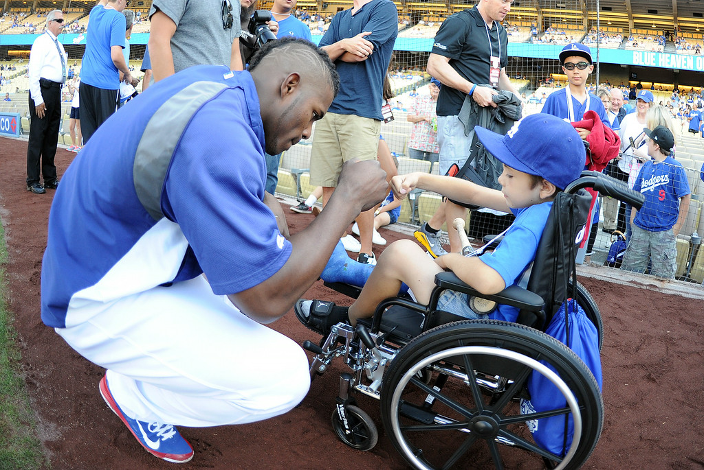 Description of . Los Angeles Dodgers' Yasiel Puig fist pumps 8 year-old Jeremiah Rivera of Riverside prior to a Major league baseball game between the San Diego Padres and the Los Angeles Dodgers on Saturday, July 12, 2014 in Los Angeles.   (Keith Birmingham/Pasadena Star-News)