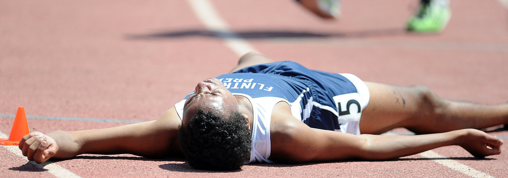 Description of . Flintrtidge Prep's Alan Yoho collapses after finishing second in the 1600 meter race during the CIF-SS track & Field championship finals in Hilmer Stadium on the campus of Mt. San Antonio College on Saturday, May 18, 2013 in Walnut, Calif.  (Keith Birmingham Pasadena Star-News)
