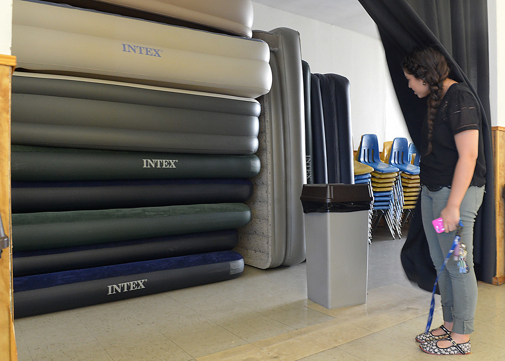 Description of . Amber Munoz shows air mattresses stacked up at St Catherine of Siena in Rialto where she says they are ready to receive immigrant children and families. A Fontana church, St. Joseph's Catholic Church, is caring for a group of immigrants from Central America, and volunteers at two other Inland churches, including St. Catherine of Siena, are making preparations to help. A bus transported 46 immigrants, mostly children, this morning Thursday July 10, 2014 to St. Joseph's. (Photo by Rick Sforza/The Sun)