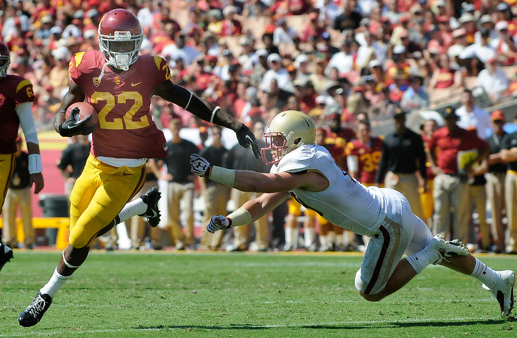 Description of . USC #22 Justin Davis gets past Boston #21 Manuel Asprilla, on his way to a TD in the 3rd quarter. USC defeated Boston College 35-7 in a game played at the Coliseum in Los Angeles, CA. 9/14/2013. photo by (John McCoy/Los Angeles Daily News)