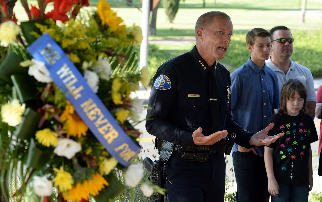 Description of . Friends and police officers pay tribute to Glendora Police Officer Louis Anthony Pompei at his memorial on Puente Street in San Dimas Monday afternoon June 9, 2014. Pompei was killed in the line of duty at a near by market during a robbery attempt in June 1995. (Will Lester/Inland Valley Daily Bulletin)