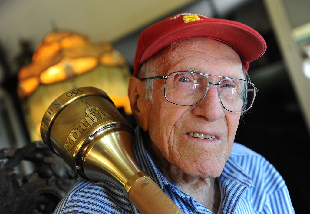 Description of . Louis Zamperini, 94, at his Hollywood home. The flame still burns in him as he holds the olympic torch he carried at the 1984 Olympic Games. Photo by Brad Graverson 11-7-10