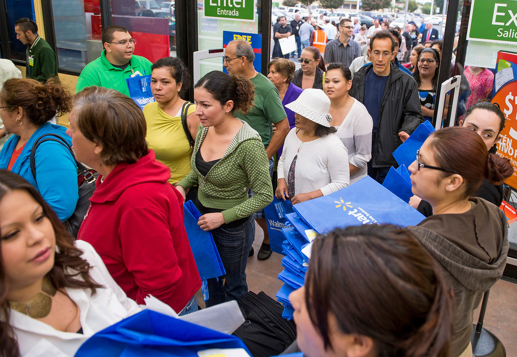 Description of . Shopper pour into the Walmart Neighborhood Market during their grand opening at 1425 N. Hacienda Boulevard in La Puente, Calif. October 2, 2013.  (Staff photo by Leo Jarzomb/SGV Tribune)