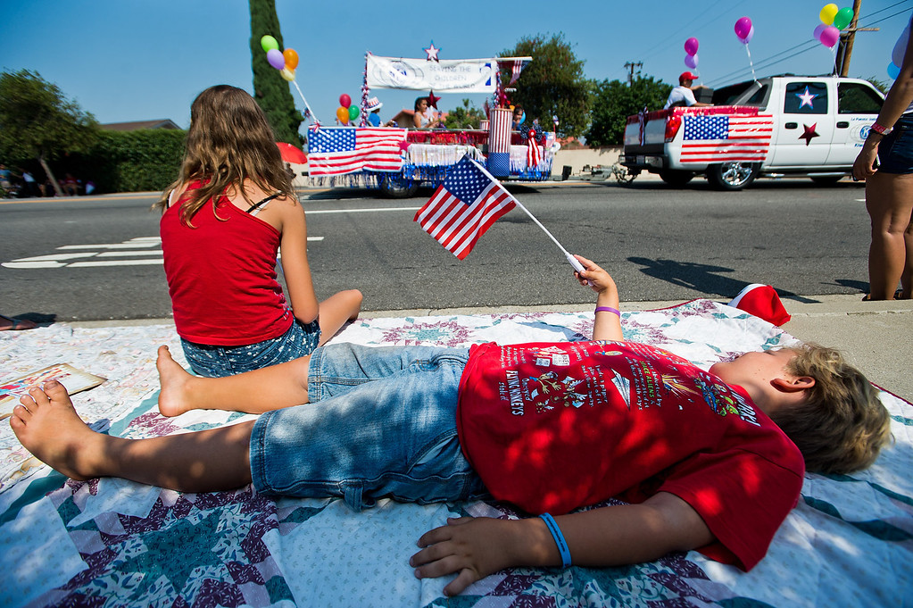 Description of . Jacob Donoghue, 6, of Buena Park, lays on sidewalk as I Love America parade rolls down Stimson Avenue in Hacienda Heights on Thursday, July 4, 2013. (SGVN/Staff photo by Watchara Phomicinda)