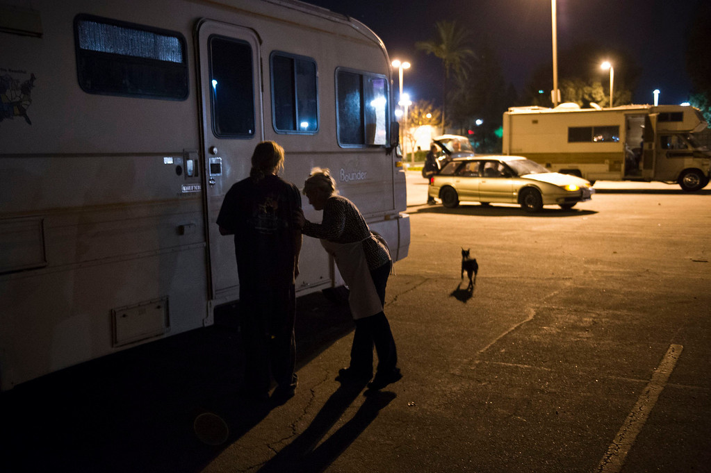 Description of . Nicolette Wingert brings food to a homeless man who lives in his motorhome behind a department store in Covina on Wednesday night, Nov. 27, 2013. Nicolette Wingert has been feeding the homeless six days a week for the past seven years with Nurses4Christ, a nonprofit organization she founded in 2006. She and Phillip Stern of Glendora have been going every day since 2008, feeding homeless people sandwiches and hot food; giving them bottles of water, clothes and blankets. (Photo by Watchara Phomicinda/San Gabriel Valley Tribune)