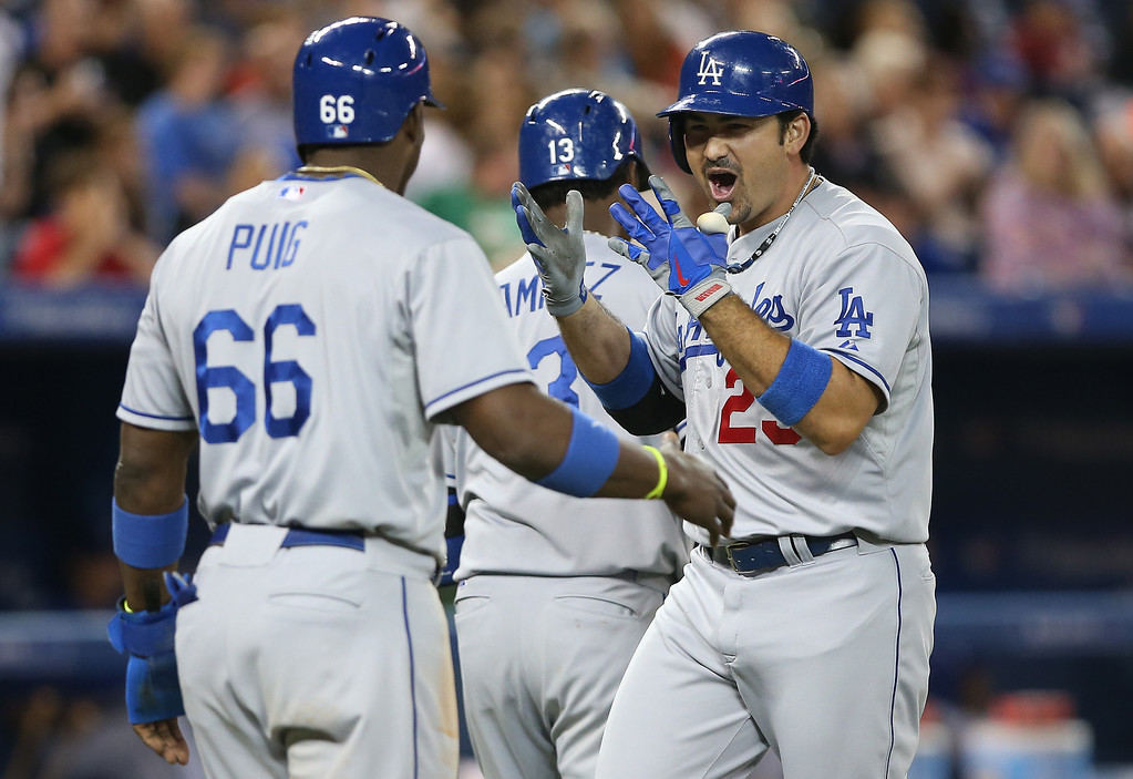 Description of . Adrian Gonzalez #23 of the Los Angeles Dodgers is congratulated by Yasiel Puig #66 after hitting a three-run home run in the eighth inning during MLB game action against the Toronto Blue Jays on July 23, 2013 at Rogers Centre in Toronto, Ontario, Canada. Dodgers won 10-9.  (Photo by Tom Szczerbowski/Getty Images)