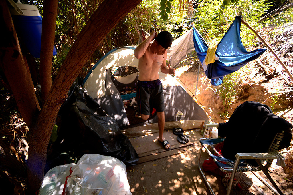 Description of . Anthony Ethridge, 45, emerges from a tent at a homeless camp along the I-210 freeway in San Bernardino August 14, 2013.  The camp is hidden from view as it is nestled between a freeway embankment and a retaining wall belonging to a set of apartments.  GABREL LUIS ACOSTA/STAFF PHOTOGRAPHER.