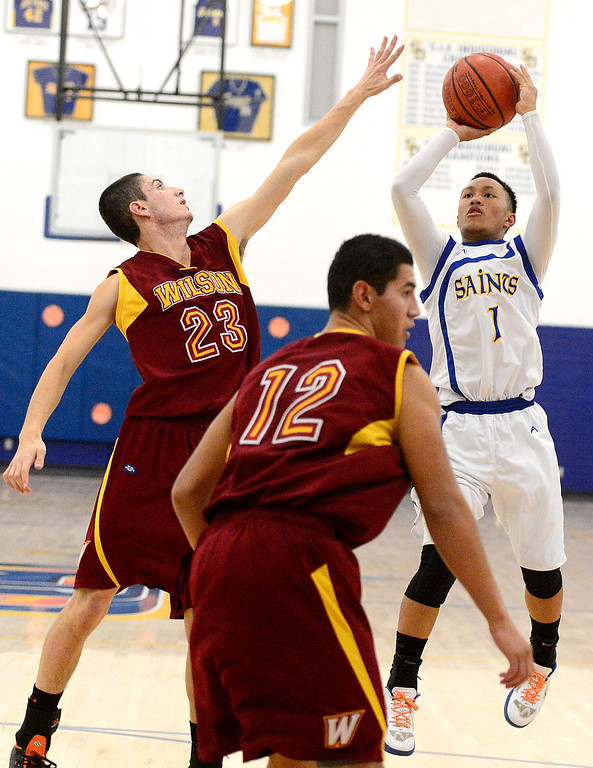 Description of . Wilson's Erick Ramos (23) attempts to block San Dimas' Ryan Ocampo (1) from making a shot as Wilson defeats San Dimas 45-43 Friday night, January 10, 2014 at San Dimas High School.  (Photo by Sarah Reingewirtz/Pasadena Star-News)