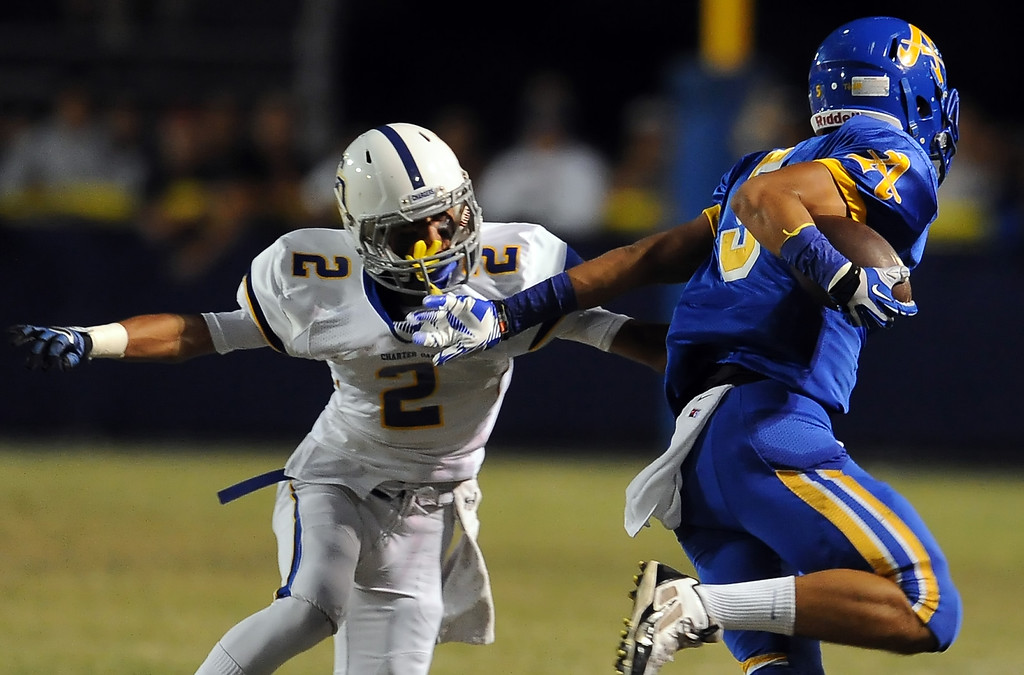 Description of . Bishop Amat's Anthony Camargo (C) (5) runs past Charter Oak's Candy Nava (2) in the first half of a prep football game at Bishop Amat High School in La Puente, Calif. on Friday, Sept. 20, 2013.    (Photo by Keith Birmingham/Pasadena Star-News)
