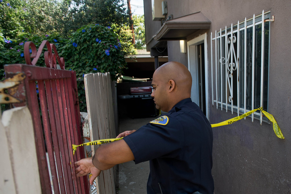 Description of . A Pomona Police officer puts up crime scene tape as police investigate an early morning shooting death of a woman in an apartment complex in the 700 block of San Francisco Avenue in Pomona on Monday, June 14, 2014. The body was found in the carport area behind the complex. (Photo by Watchara Phomicinda/ San Gabriel Valley Tribune)