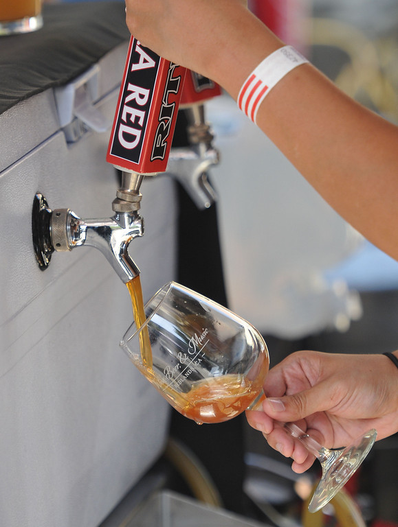Description of . (John Valenzuela/Staff Photographer)  Adrienne Macalinao of Ritual Brewery, pours a glass of their Extra Red Ale during the Redlands Wine, Beer, and Music event at Ed Hales Park in downtown Redlands, Saturday, June 22, 2013.