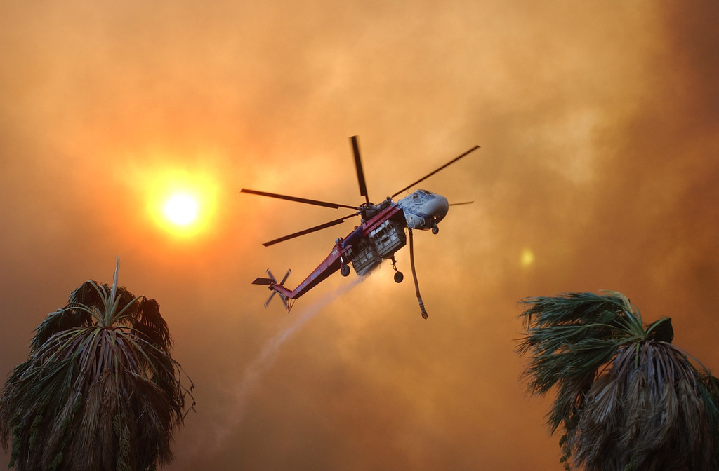 Description of . Ten years ago this month the arson caused Old Fire, fanned by Santa Ana winds burned thousands of acres, destroyed hundreds of homes and caused six deaths. The fire burned homes in San Bernardino, Highland, Cedar Glen, Crestline, Running Springs and Lake Arrowhead and forced the evacuation of thousand of residents.  A sky crane helicopter flies across a smoke filled sky after dropping a load of water while fighting the Old Fire in San Bernardino. (Staff file photo/The Sun)