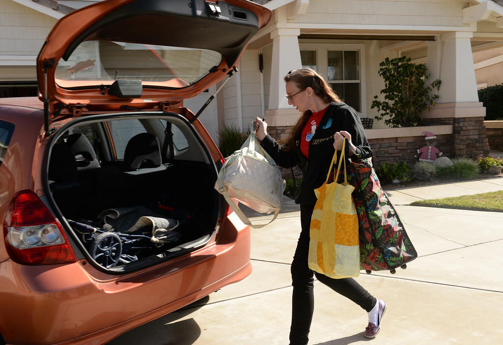 Description of . Amanda Hartrell loads up her vehicle as she prepares to evacuate from her home on Ridge View Drive in Azusa on Thursday February 27, 2014. (Staff Photo by Keith Durflinger/San Gabriel Valley Tribune)