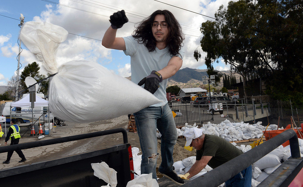 Description of . Christopher Serrano loads up sandbags with his father, Ramiro, at the Glendora City Yard as they plan to block off their driveway on Thursday February 27, 2014. (Staff Photo by Keith Durflinger/San Gabriel Valley Tribune)