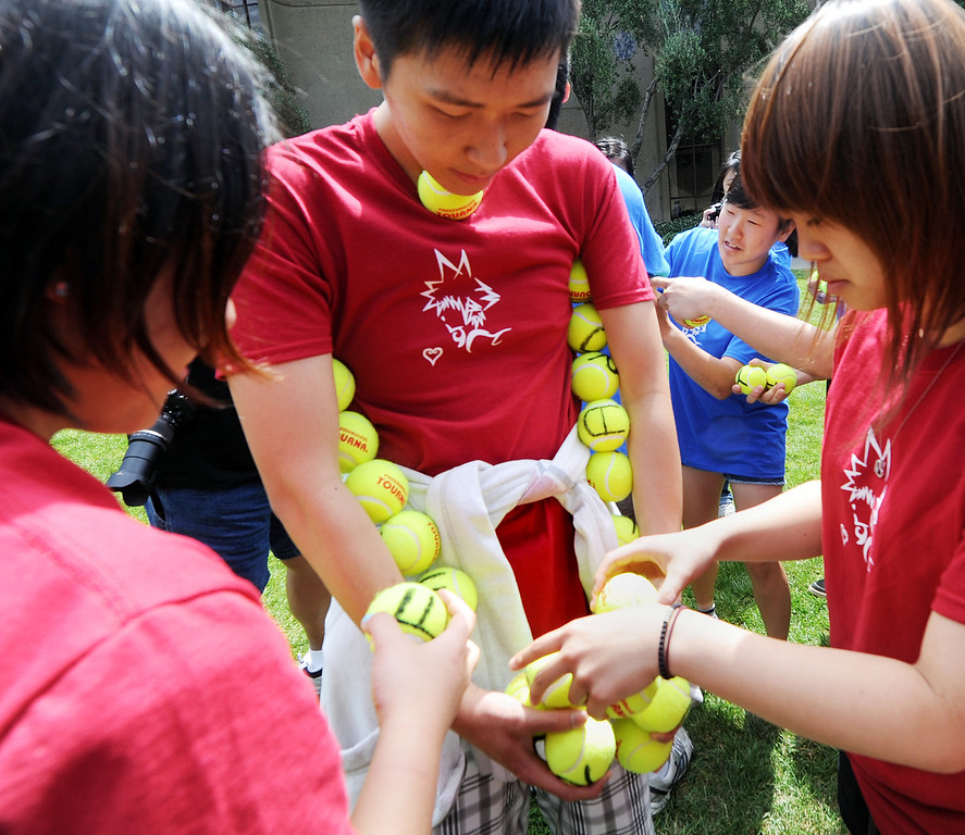 Description of . A contest to hold the most tennis balls without dropping one for Kindom Hearts Stack during Ditch Day. A fun-filled day of antics and escapades, Ditch Day is one of Caltech's oldest traditions – a cross between Animal House and a science fair! Friday, May 24, 2013. Caltech seniors ditch their classes while underclassmen devote their entire day to quirky pranks and attempting to solve elaborate puzzles, mazes, quests, and other challenging hijinks that seniors have devised and left behind for them.This year's activities include a laser maze, sledgehammer brick building demolition, shopping cart race, sumo tournament, roof rappelling, hovercraft human bowling, teleportation and time-travel puzzles, and much more.(SGVN/Photo by Walt Mancini)