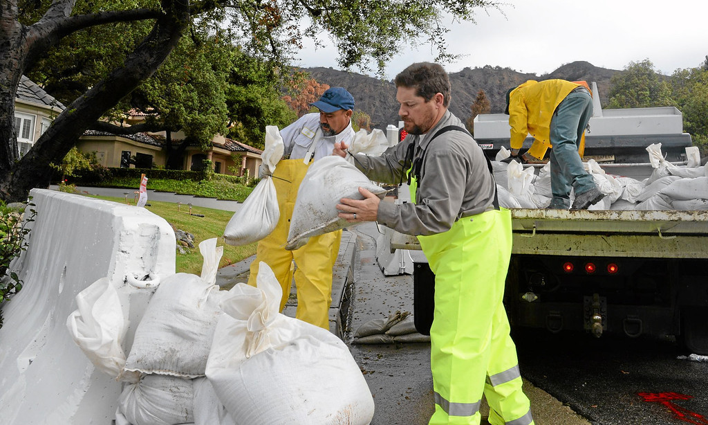 Description of . City workers place additional sandbags around K-rails at Englewild Drive and Rose Drive in Glendora in preparation of the oncoming storm on Thursday February 27, 2014. (Staff Photo by Keith Durflinger/San Gabriel Valley Tribune)