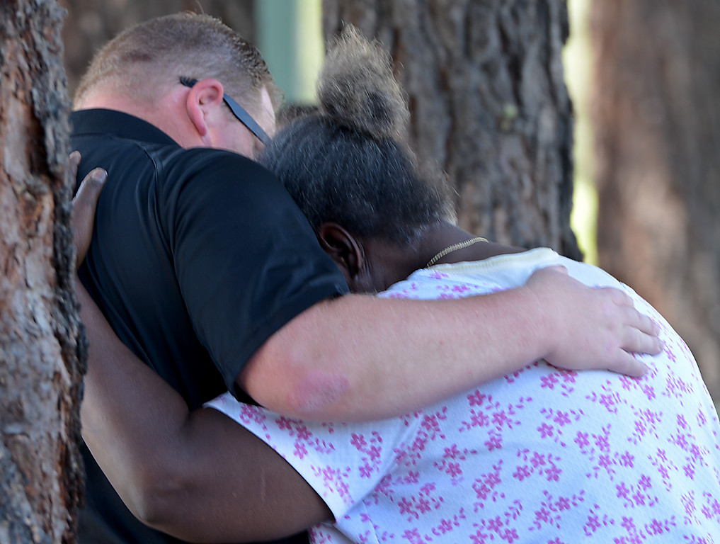 Description of . Cynthia Johnson, the mother of a shooting victim, is comforted by David McCarthy, a San Bernardino county sheriff's deputy coroner, as her son's body is removed. San Bernardino police are investigating a shooting that left three man dead. The three were killed following a shooting early Friday, in the 1900 block of South Diners Court, police near Hospitality Lane in San Bernardino (Photo by Rick Sforza/The Sun)