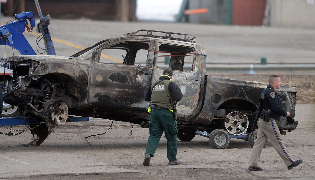 Description of . Law enforcement officers inspect a burned out Nissan pickup truck believed to be owned by ex-LAPD officer Christopher Dorner at Bear Mountain in Big Bear Thursday February 7, 2013.(Staff photo by Will Lester/Inland Valley Daily Bulletin)