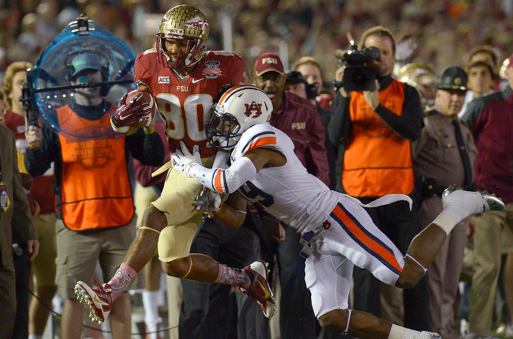 Description of . Florida State's Rashad Greene is knocked out of bounds by Auburn's Ryan White during the first half of the 2014 Vizio BCS National Championship January 6, 2014 in Pasadena CA.(Andy Holzman/Los Angeles Daily News)
