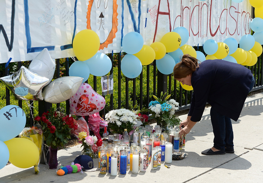 Description of . Maria Avila, the mother of a student at El Monte High School, places a candle at a memorial near the front gate of the school. Students at El Monte High School brought flowers, candles and other items in remembering Adrian Castro, a Senior student who was killed in bus crash in Northern California that took the lives of 10 people. El Monte, CA. 4/13/2014(Photo by John McCoy / Los Angeles Daily News)