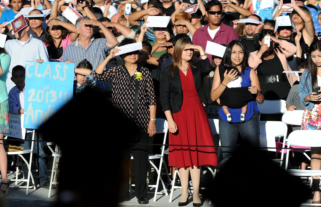 Description of . Family and friends shade their eyes as they look for their graduate during the Vail High School commencement at Vail High School on Tuesday, June 18, 2013 in Montebello, Calif.