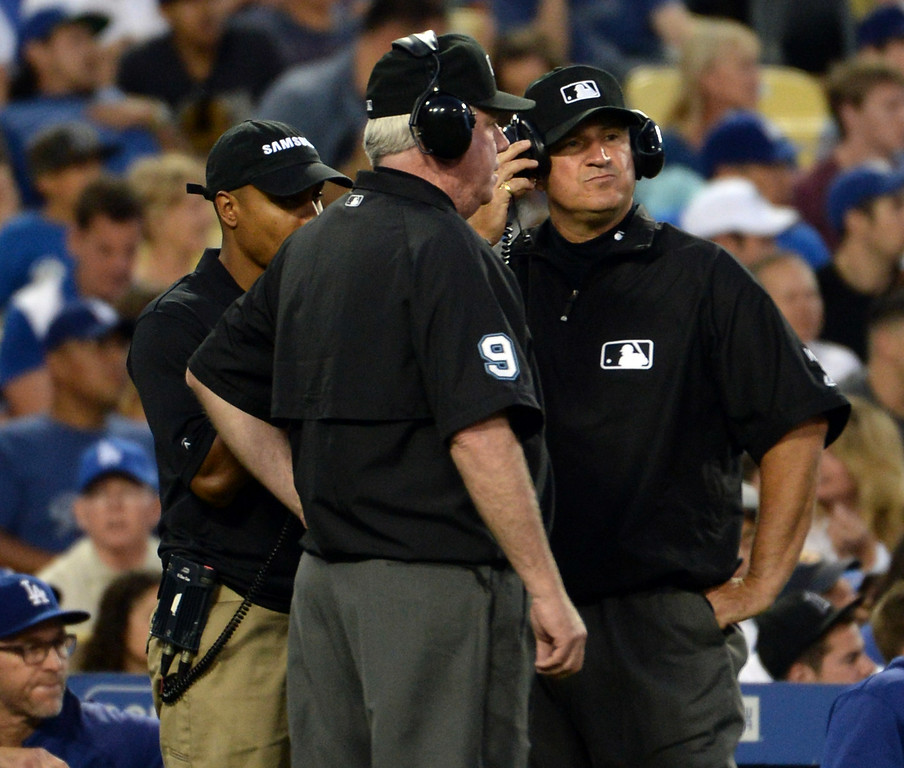 Description of . Umpires wait for a decision on a instant replay call in the fourth inning of a Major league baseball game between the San Diego Padres and the Los Angeles Dodgers on Saturday, July 12, 2014 in Los Angeles.   (Keith Birmingham/Pasadena Star-News)