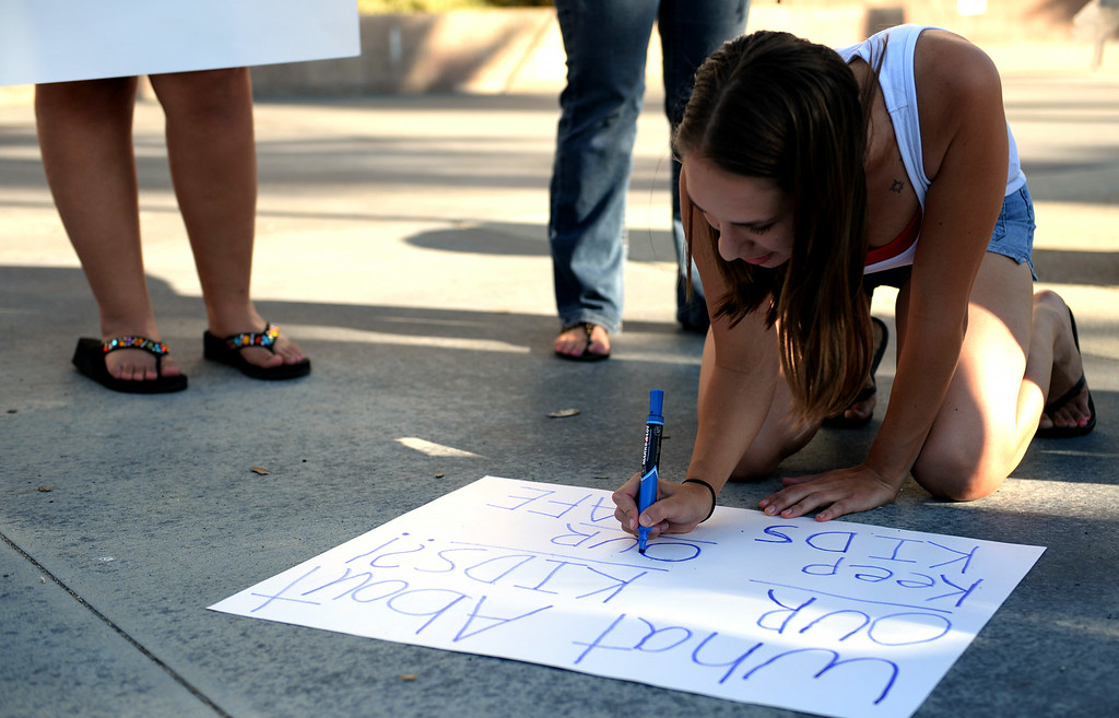 Description of . Lori Espinosa, 22, of Murrieta, creates a sign prior to the start of a town hall meeting on Wednesday, July 2, 2014 at Murrieta Mesa High School in Murrieta, Ca. The meeting is being held in response to immigrants who were being processed through a Texas Border Patrol Station and delivered to the Murrieta Border Patrol Station on Tuesday. (Micah Escamilla/The Sun)