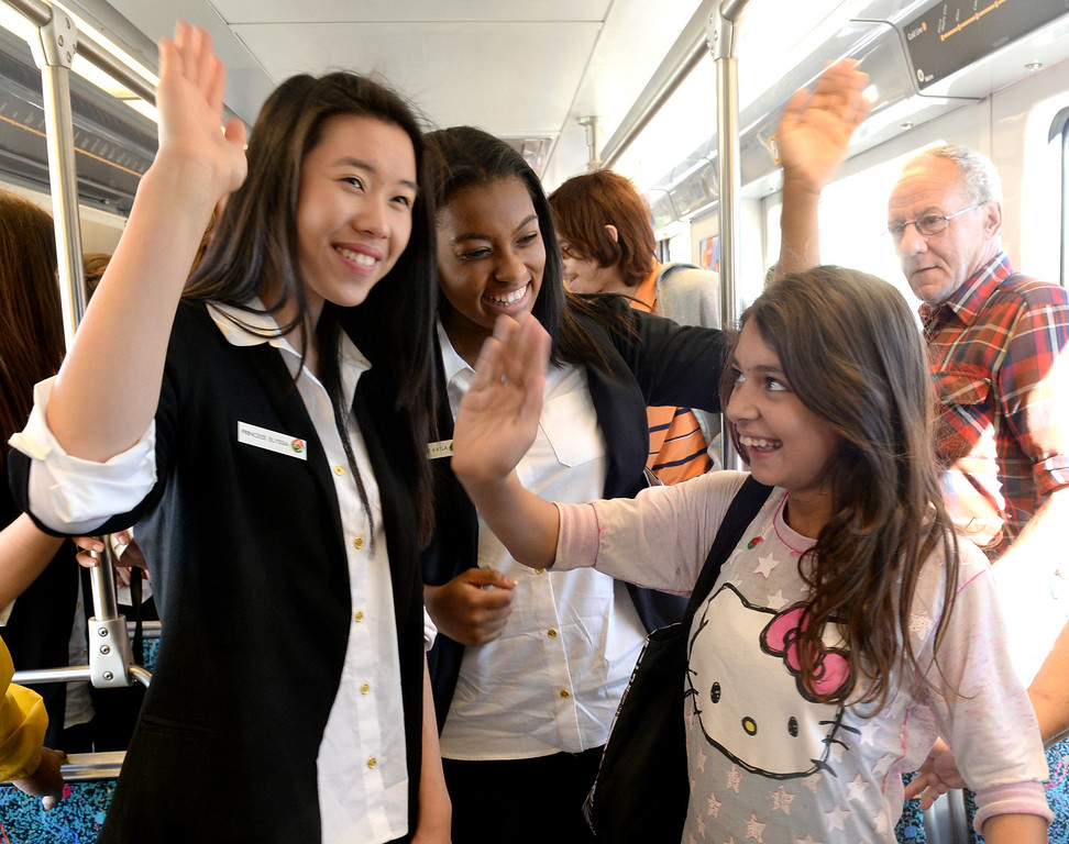 Description of . The 2014 Tournament of Roses Princesses Elyssia Widjaja, left, and Kayla Johnson-Granberry, center, teach Karla White, 11, how to wave as they ride the Metro gold Line from Union Station in Los Angeles on Friday December 27, 2013. The event is to commemorate the 10th official year of Metro Rail service to the Tournament of Roses parade events at Union Station. (Staff Photo by Keith Durflinger/Pasadena Star-News)