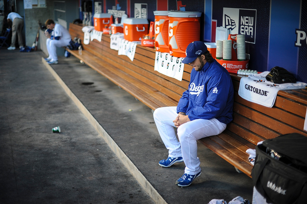 Description of . The Dodgers' Clayton Kershaw waits on the bench before the start of game 4 of Dodgers vs Atlanta Monday, October 7, 2013 ( Photo by Andy Holzman/Los Angeles Daily News )