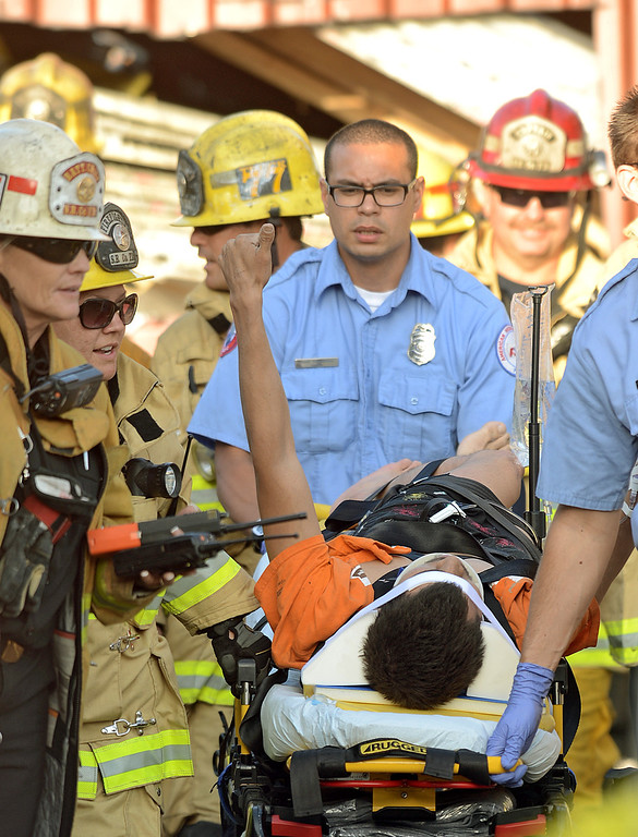 Description of . A 20 year old man gives a thumbs up after being rescued by San Bernardino County Firefighters from being crushed by 2000 pounds of granite in a trailer at a contractors business in Fontana April 30, 2013.(Thomas R. Cordova/Staff Photographer)