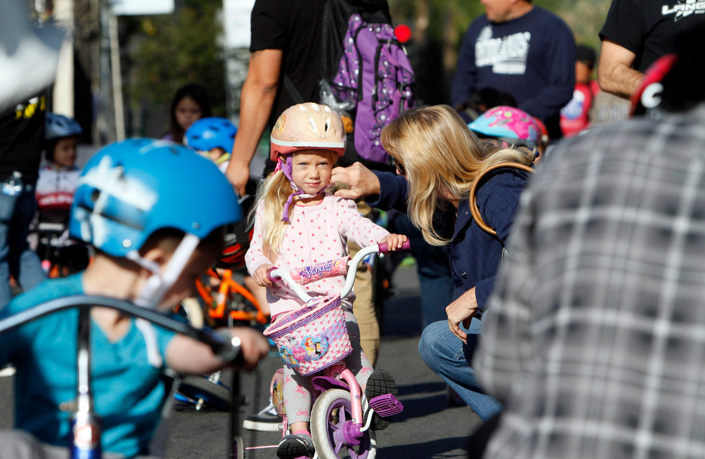Description of . A rider has her helmet adjusted before the start of the public race portion of the Redlands Bicycle Classic on Saturday, April 5, 2014 in Redlands, Ca. (Photo by Micah Escamilla for the Redlands Daily Facts)