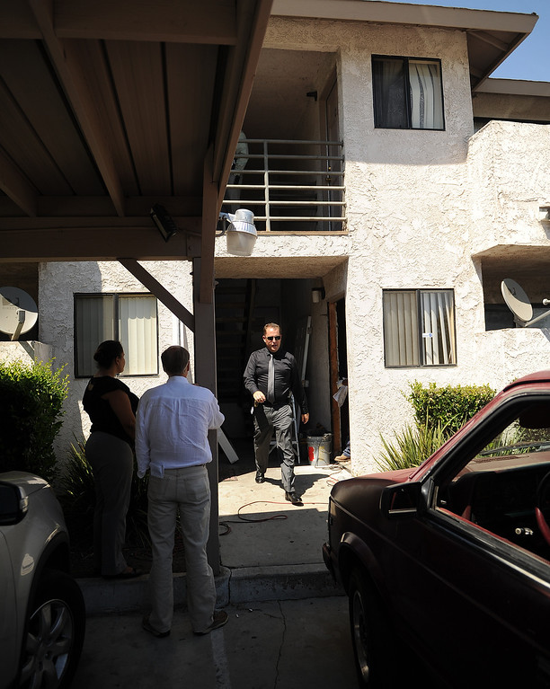 Description of . Fontana Police Detective walks past the apartment Wednesday, where resident Domonique Newburn, 31, was found dead, in the 7900 block of Bennett Avenue around 4:30 p.m. Tuesday while police were investigating a report of a disturbance. (LaFonzo Carter/ Staff Photographer)