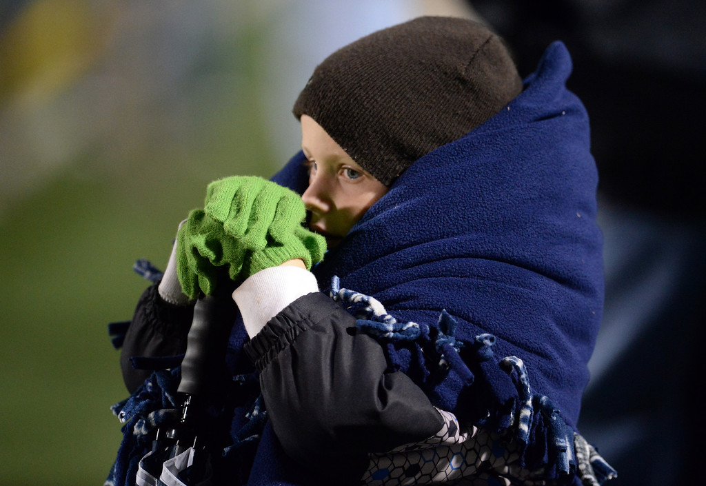 Description of . A young San Dimas fans stays warm in the first half of a CIF-SS Mid-Valley Division championship football game against Paraclete at San Dimas High School in San Dimas, Calif., on Friday, Dec. 6, 2013.   (Keith Birmingham Pasadena Star-News)
