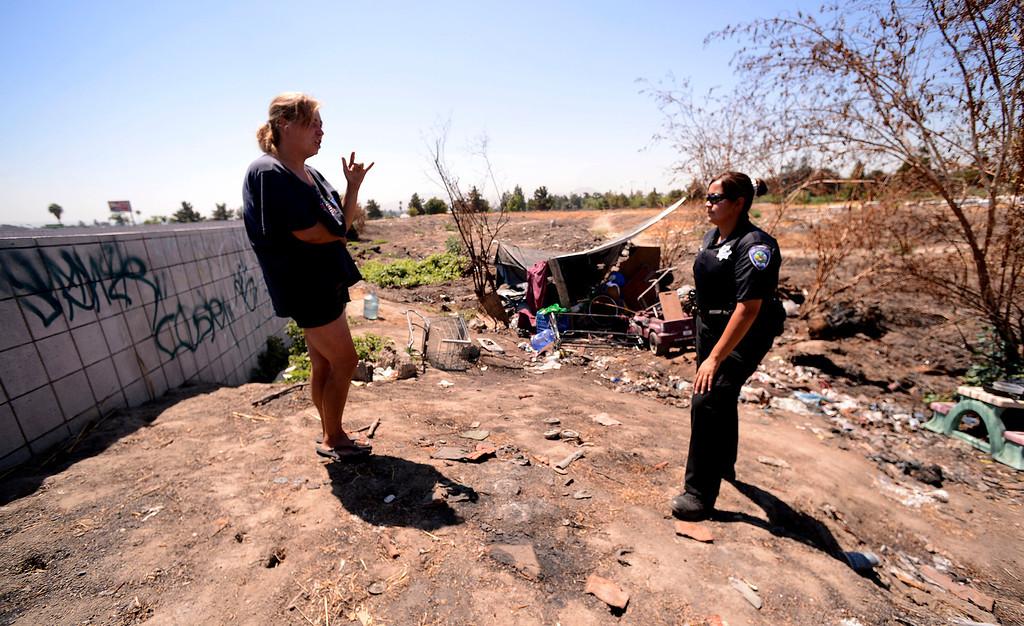 Description of . Dawna Bonner, 30, speaks with San Bernardino Police Officer and Homeless Advocate Sochilt Martinez outside a homeless camp along Ninth Street in San Bernardino August 14, 2013. GABREL LUIS ACOSTA/STAFF PHOTOGRAPHER.