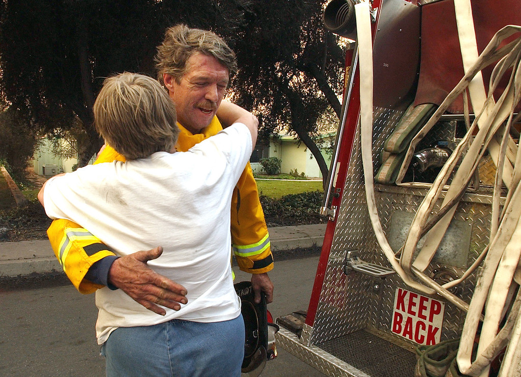 Description of . Ten years ago this month the arson caused Old Fire, fanned by Santa Ana winds burned thousands of acres, destroyed hundreds of homes and caused six deaths. The fire burned homes in San Bernardino, Highland, Cedar Glen, Crestline, Running Springs and Lake Arrowhead and forced the evacuation of thousand of residents. San Francisco Fire Department Captain John Staudt is hugged by resident Carol Peterson after Staudt's crew hosed out a hot spot in the remains of the Peterson home Sunday morning. The Peterson home was destroyed by the Old Fire Saturday. (Staff file photo/The Sun)