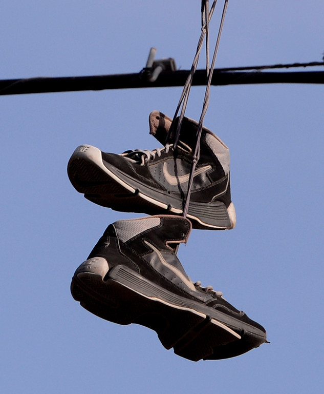Description of . Shoes hang from telephone wires along the 200 block of Tenth Street as seen during a county wide police sweep in San Bernardino August 2, 2013. GABRIEL LUIS ACOSTA/STAFF PHOTOGRAPHER.