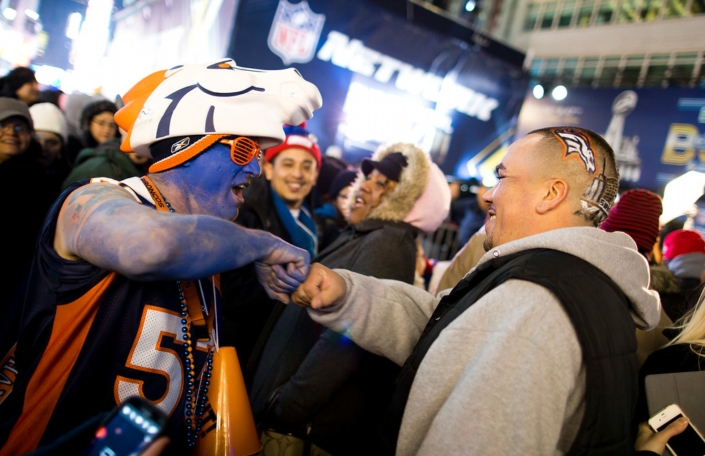 Description of . Denver Broncos fans Lonnie Moreno, left, of Denver, and Steve Aviles, of Union City, N.J., bump fists as they tour the Super Bowl Boulevard in Times Square, Friday, Jan. 31, 2014, in New York. The Broncos play the Seattle Seahawks on Sunday in NFL football\'s Super Bowl in East Rutherford, N.J. (AP Photo/ Evan Vucci)