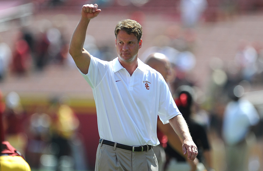 Description of . Southern California head coach Lane Kiffin holds his fist in the air prior to a NCAA college football game against Boston College in the Los Angeles Memorial Coliseum in Los Angeles, on Saturday, Sept. 14, 2013.