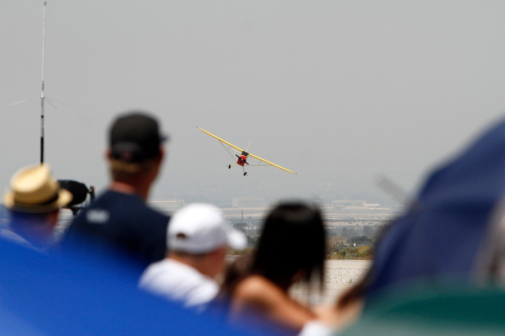 Description of . AirFest attendees watch as Kent Pietsch gives an aerial performance in an Interstate Cadet aircraft during the Hangar 24 AirFest and 6th Anniversary Celebration on Saturday, May 17, 2014 at the Redlands Municipal Airport in Redlands, Ca. (Photo by Micah Escamilla/Redlands Daily Facts)