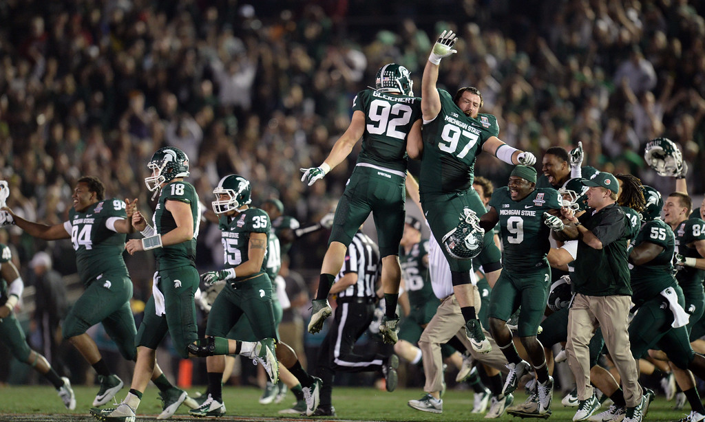 Description of . Michigan State players run on to the field as time expires during the 100th Rose Bowl game in Pasadena Wednesday, January 1, 2014. Michigan State defeated Stanford 24-20. (Photo by Hans Gutknecht/Los Angeles Daily News)